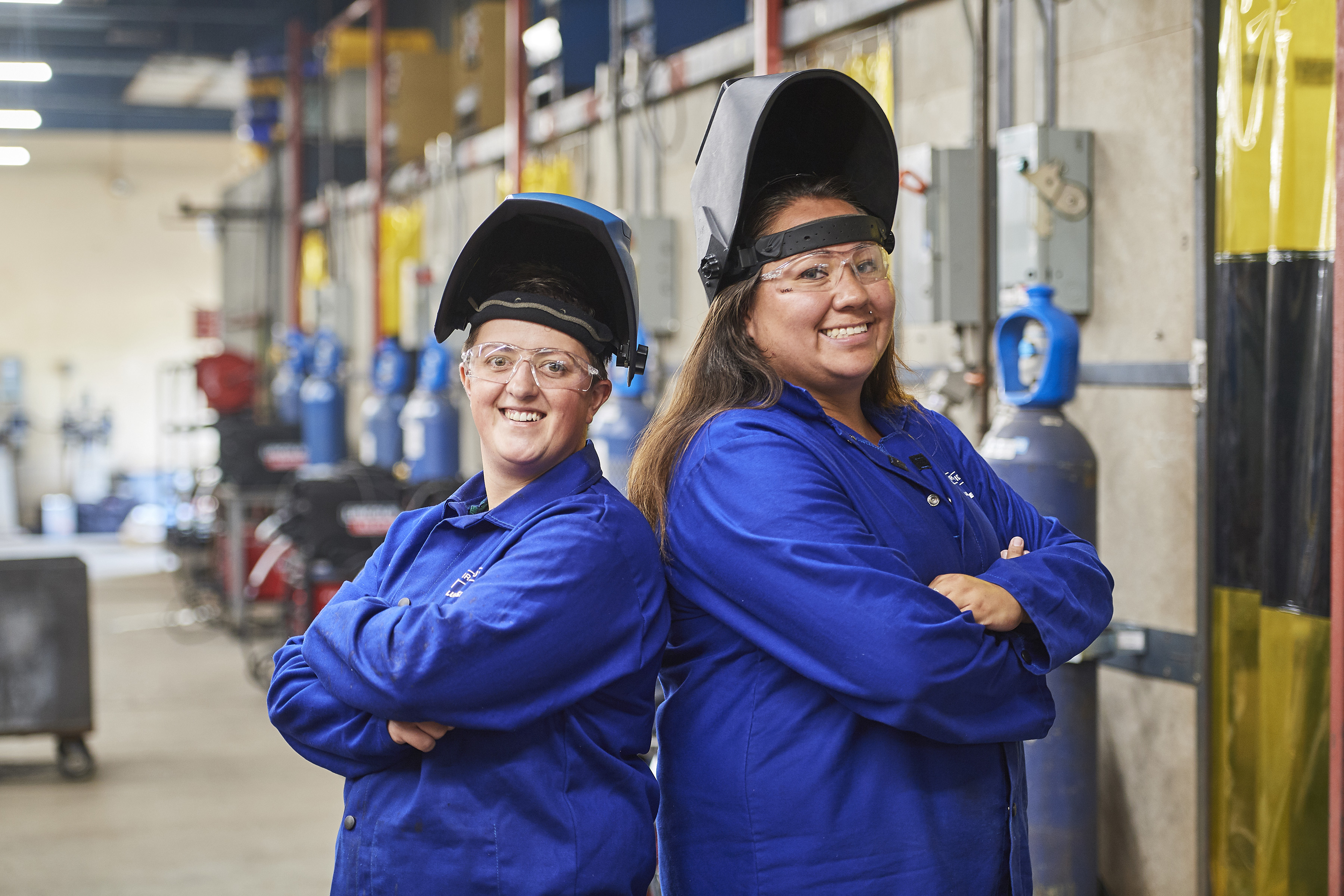 Two welding students standing back to back in welding bay